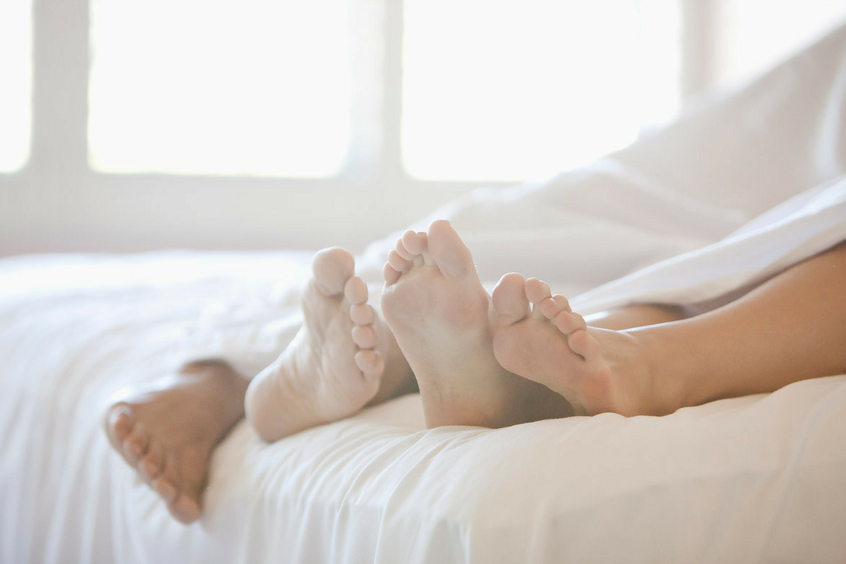 2 pairs of feet showing under white sheets - Playful Loving